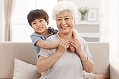 Cute little boy and grandmother in the living room