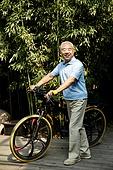 An old man pushing a bicycle