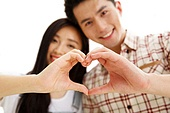 The young lovers do heart-shaped gestures