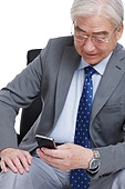 A business old man holding a mobile phone sat in the boss chair