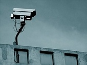 Security surveillance camera on rooftop of urban building.