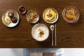 음식, 명절 (한국문화), 새해 (홀리데이), 명절음식, 추석 (명절), 한국 (동아시아), 한국문화 (세계문화), 전통문화 (주제), 전통음식, 밥상 (한국전통), 테이블, 방석, 나무, 나무결, 탑앵글, 새해첫날 (새해), 숟가락, 젓가락, 그릇, 접시, 놋그릇 (한국전통), 떡국 (명절음식), 고명, 나물, 고사리, 도라지 (채소), 시금치, 시금치나물, 잡채, 반찬, 전, 동태전, 간장, 버섯전