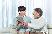 남성, 아빠 (부모), 아들, 거실, 스마트기기 (정보장비), 가르치는 (움직이는활동), 미소, 마주보기 (위치묘사)