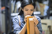 Young leather craftswoman working in studio