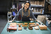 Young leather craftswoman in studio