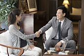 Confident businessman shaking hands with a mature woman