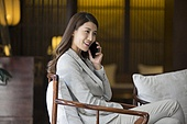 Cheerful young businesswoman talking on cell phone