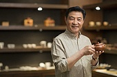 Mature man showing a teapot