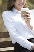 Cheerful young businesswoman drinking coffee