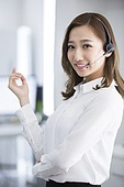Cheerful young businesswoman with headset in office