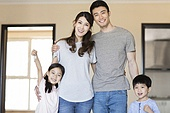 Happy young family holding keys in their new house