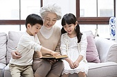 Cheerful grandmother and grandchildren reading book on sofa