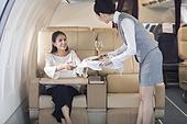 Airline stewardess serving food to passenger