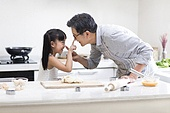 Happy little girl and grandfather baking cookies in kitchen