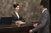 Cheerful businessman checking into hotel