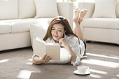 Cheerful young woman reading a book at home