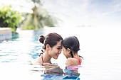 Happy mother and daughter having fun in swimming pool