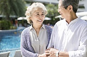 Happy senior couple walking at poolside