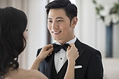 Young wife adjusting bow tie for her husband