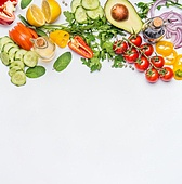 Healthy clean eating layout, vegetarian food and diet nutrition concept. Various fresh vegetables ingredients for salad on white table background, top view, border