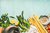 Wild garlic pasta cooking ingredients: pot with spoon, wild garlic,pasta noodles, pine nuts, tomatoes and seasoning on blue background, top view. Healthy seasonal food and eating concept