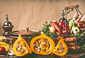 Hokkaido Pumpkins on kitchen table with cooking pot and ingredients at rustic wall background, front view. Healthy vegetarian  food and eating concept.  Autumn seasonal eating