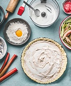 Rhubarb cake preparation. Tart baking pan with pie dough and cream fresh on kitchen table background with rolling pin, flour, egg and fresh red rhubarb stalks, top view. Seasonal cooking concept