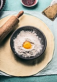 Bake concept. Dough, rolling pin and bowl with flour and egg, top view