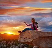 Hiker teen girl selfie smartphone on peak of mountain at sunset