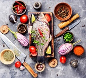 Fresh fish with ingredients for cooking on cutting board.Cooking concept.Healthy diet. Fresh raw fish and food ingredients