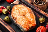 Grilled salmon with tomato, pepper and cabbage.Fish steak with vegetable garnish.Grilled fresh fish.Beautiful festive dish. Baked salmon steak