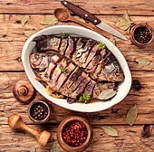 Grilled whole fish loaded with citrus, herbs and spices on rustic wooden table.Seafood concept. Carp stuffed with vegetables