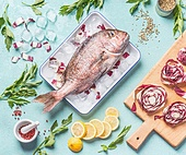 Raw whole fish in tray with ice cubes on light turquoise background with ingredients, top view. Seafood concept. Pink dorado cooking preparation