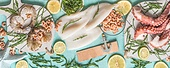 Various seafood: octopus , shrimp, squid and seaweed  on light blue background with ingredients, top view. Seafood concept