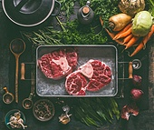 Ingredients for tasty Ham Hock Soup : raw beef meat shin with bone, root vegetables, herbs and spices on dark rustic kitchen table background with cooking spoon and cast iron pot , top view.