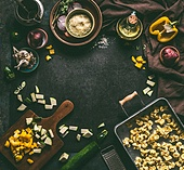 Dark food and cooking background frame with homemade vegetarian tortellini in tray on dark rustic table with vegetables ingredients and vintage  kitchen utensils, top view. Home cuisine.