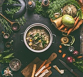 Beef and cabbage soup or stew in cast iron cooking pot on dark background with low carb vegetables, spices ingredients and wooden spoon, top view. Healthy clean low-calorie food and eating concept