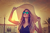 Blond teen girl sunglasses and pamela sun hat at palm tree sunset filtered image