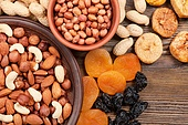 Different nuts in plates and dried fruits on a wooden background. Almond, hazelnut and peanut.
