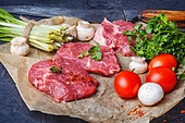 Raw meat home beef. Sliced raw veal steaks with ramson and tomatoes