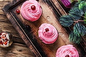 Homemade christmas cupcakes. Christmas cupcakes and decorations on vintage wooden background