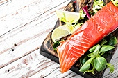 Delicious salmon fillet. Salmon with vegetables and lettuce on cutting board.Healthy food