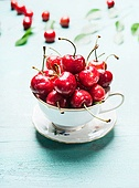 Cup with fresh ripe cherry berries, front view, close up