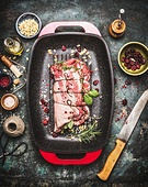 Raw Meat roast preparation in  roaster pan with cooking ingredients and seasoning on dark rustic background with butcher knife, top view