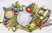 Healthy vegetarian eating with various vegetables and Pearl barley. Porridge or salad ingredients for tasty cooking around round cutting board, top view. Clean eating or diet nutrition concept