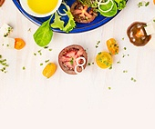 Tomatoes salad making with oil and cress on white wooden background, top view