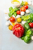Tomatoes various with fresh basil and mozzarella on blue wooden background