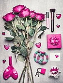 Pink Female accessories with roses flowers, makeup , hearts.  Top view on messy woman boudoir , fashion blogger or  modern dating woman set on gray background.