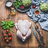 Raw whole chicken with vegetables and ingredients on wooden kitchen table for tasty cooking, top view