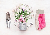 Gardening workspace, garden tools with flowers and watering can on white wooden background, top view, flat lay
